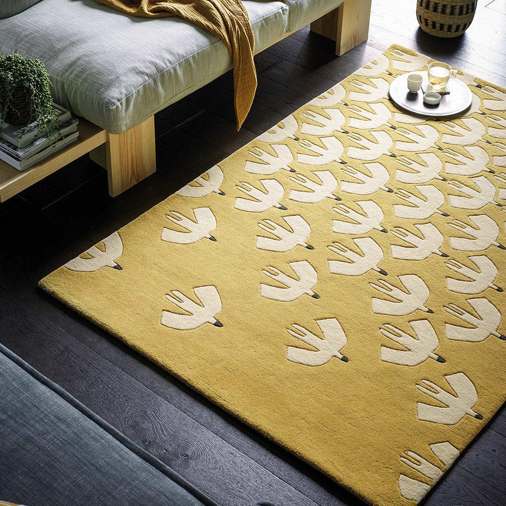 alfombra amarilla con pájaros blancos